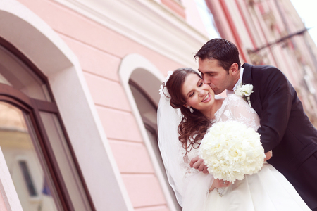 beautiful bride: Beautiful bride and groom embracing in city Stock Photo