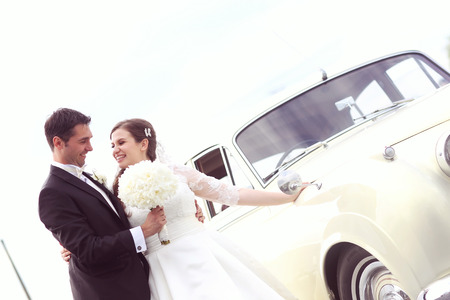 two tone: Beautiful bride and groom embracing near classic car