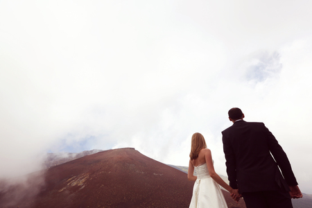 multi story: Bride and groom near mountains Stock Photo