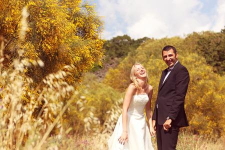 Joyful bride and groom having fun in nature