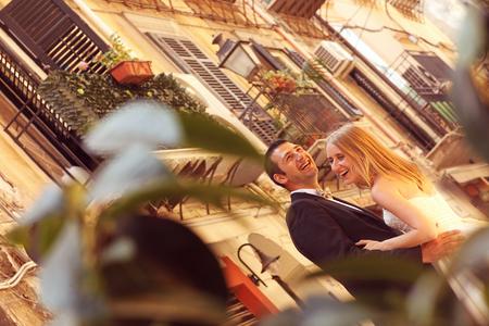 multi story: Joyful  bride and groom embracing in old city