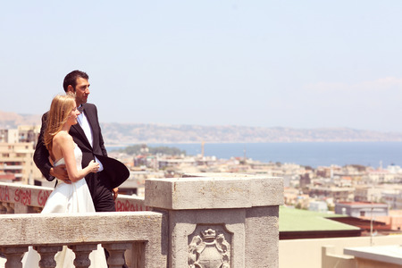 Joyful  bride and groom embracing in old city