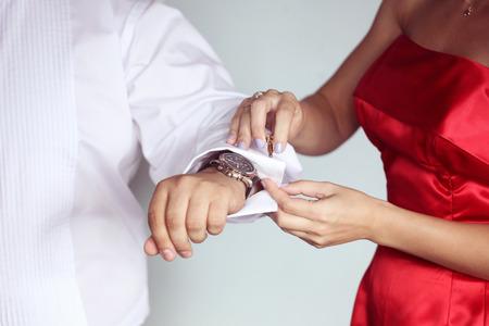 cuff links: Groom getting ready for wedding puttin on cuff links Stock Photo