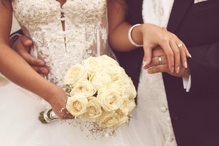 Beautiful bride and groom with bouquet on wedding day holding hands