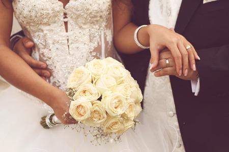 Schöne Braut und Bräutigam mit Blumenstrauß am Hochzeitstag Händchen haltend