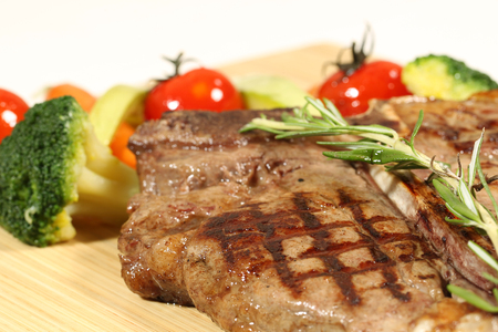 flesh eating animal: Succulent thick juicy portions of grilled fillet steak served with tomatoes and roast vegetables on an wooden board Stock Photo