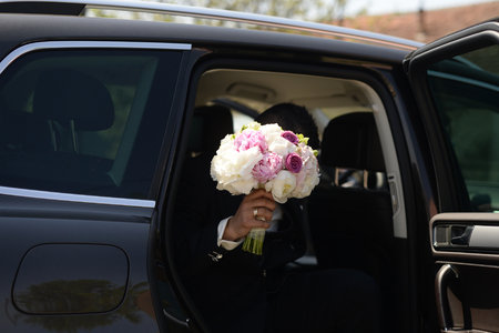 getting out: Groom getting out of the car with beautiful bridal bouquet for the bride