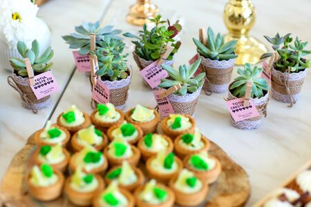 Delicious wedding reception candy bar dessert table full with cakes and sweets and a candles Standard-Bild - 140566129