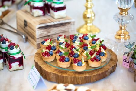 Delicious wedding reception candy bar dessert table full with cakes and sweets and a candles Standard-Bild - 140566136