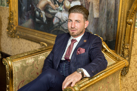 Handsome man posing on armchair in luxury hotel room