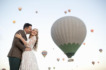 Beautiful wedding couple posing in nature near balloons