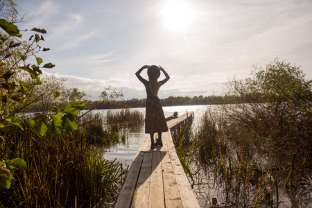 Beautiful girl posing on dock at sunny day