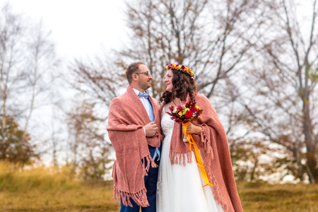 Beautiful wedding couple covered in pink blanket posing in countryside 免版税图像