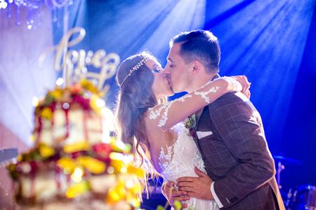 Beautiful wedding couple posing indoor with wedding cake
