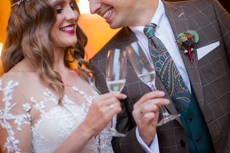 glass of wine in hands of beautiful bride and handsome groom