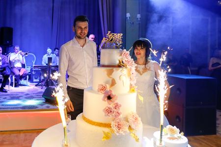 Groom and bride taste the wedding cake