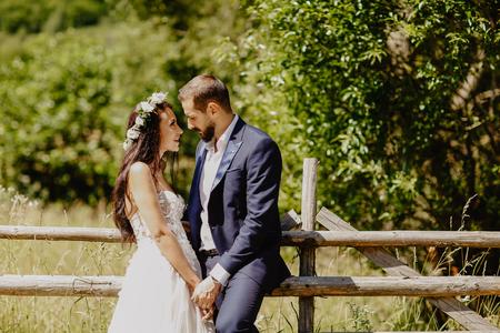 Beautiful wedding couple posing in sun near forest