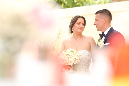 Beautiful wedding couple posing outside in park, Bride with bouquet of flowers in hands