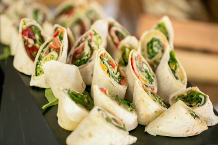 Delicious wrap with salad and bacon on table