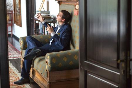 Happy man sitting on armchair in hotel