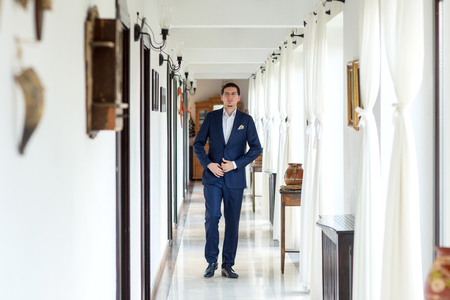 Happy groom in the hall of the hotel