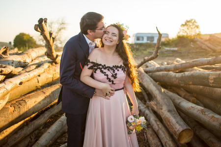 Beautiful young wedding couple, bride and groom posing near wooden cut