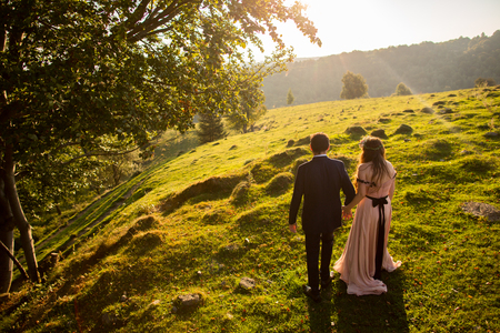 Beautiful wedding couple posing on green hills