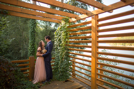 Beautiful wedding couple posing outdoor in forest on wooden dock
