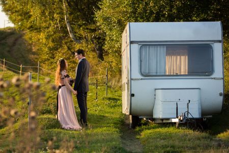 Wedding couple posing with camper van in forest Фото со стока
