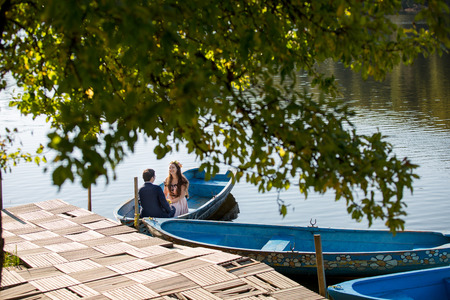 Wedding couple posing on boat in river Stock Photo
