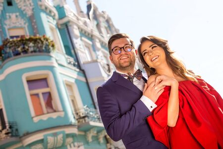 Romantic couple posing outdoor on streets, beautiful girl in red dress and handsome man in blue suit