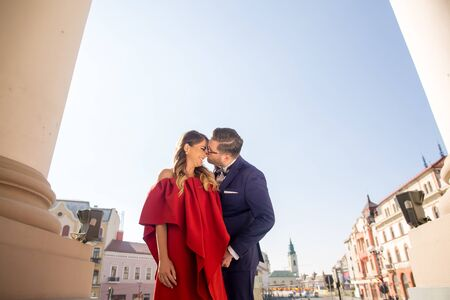 Beautiful couple posing outdoor, happy woman in red dress and handsome man posing in blue suit