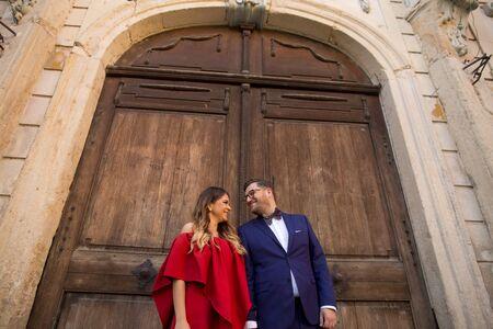 In love wedding couple posing outdoor in front of old castle wooden gate Banco de Imagens