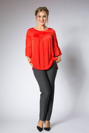 Beautiful blonde model posing in red blouse and gray pants Stock Photo