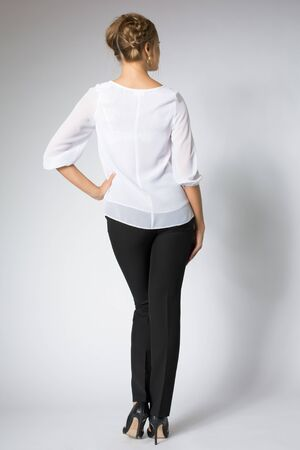 Stylish woman posing in white shirt and black pants