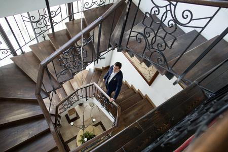 Man in tuxedo posing on stairs in hotel
