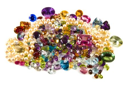 A large group of mixed faceted gemstones with pearls on a white background