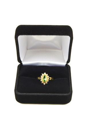tsavorite: A tsavorite garnet surrounded by diamonds in a ring in a box on a white background