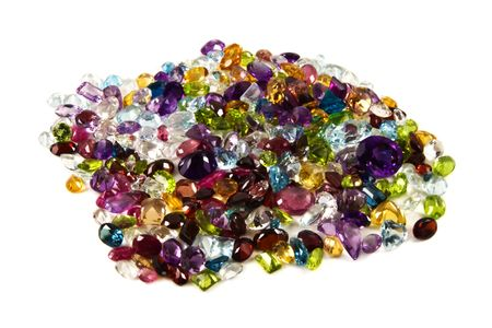 zircon: A large grouping of faceted gemstones on a white background