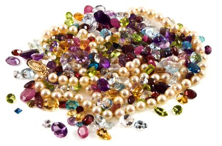 spinel: A large group of mixed faceted gemstones with pearls on a white background