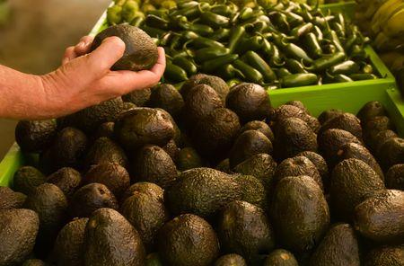 A mans hand choosing an avocado