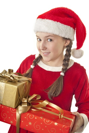Beautiful girl dressed in Christmas clothes and red santa hat with presents in her hands isolated on white background photo