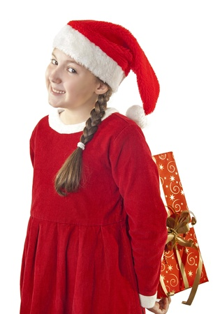 hat new year s eve: Beautiful girl dressed in Christmas clothes and red santa hat with present behind her back isolated on white background