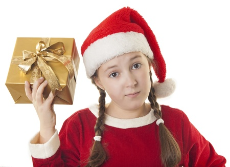 Beautiful girl dressed in Christmas clothes and red santa hat with present in her hand isolated on white background photo