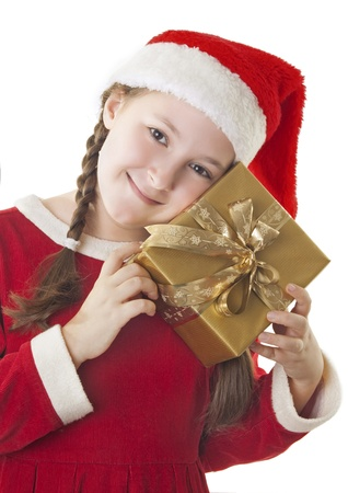 hat new year s eve: Beautiful girl dressed in Christmas clothes and red santa hat with present in her hands isolated on white background Stock Photo