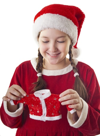 Beautiful girl dressed in Christmas clothes and red santa hat holding little santa clothes in her hands isolated on white background photo