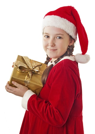 Beautiful girl dressed in Christmas clothes and red santa hat with present in her hands isolated on white background photo