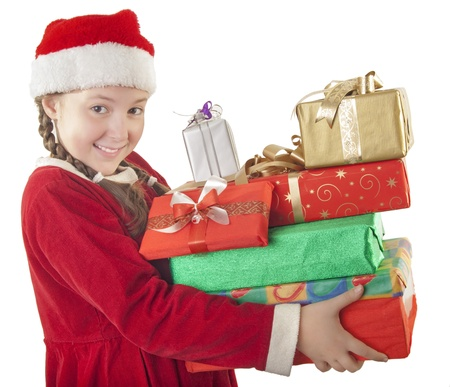 Beautiful girl dressed in Christmas clothes and red santa hat with bunch of presents in her hands isolated on white background photo