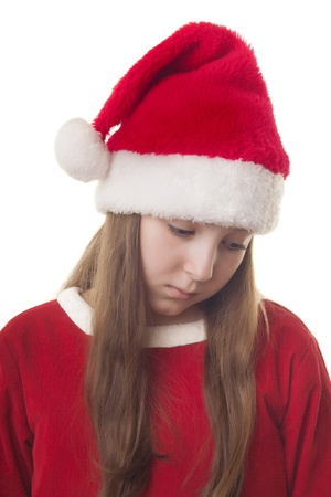 hat new year s eve: Beautiful girl dressed in Christmas clothes and red santa hat looking down expressing sadness isolated on white background