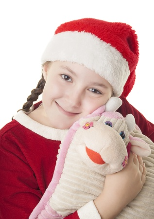 Beautiful girl dressed in Christmas clothes and red santa hat hugging cute cow pillow isolated on white background photo